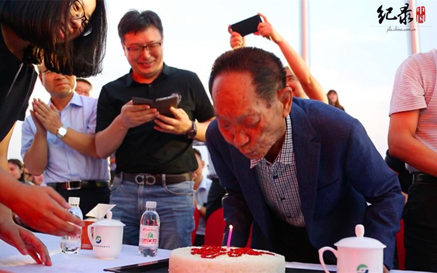 """生日蛋糕完全用大米制作,蛋糕表面用枸杞拼出""""米""""字,寓意时刻不忘心中的稻田梦。(袁老先生吹蜡烛许下心愿 晗硕摄)"""